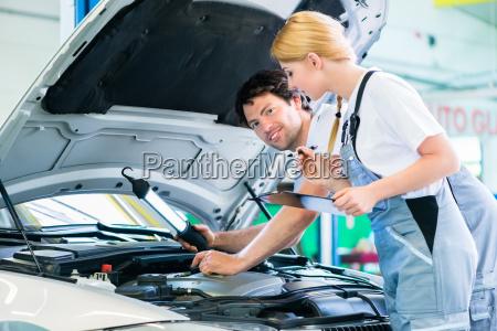 mechanic team working in car workshop