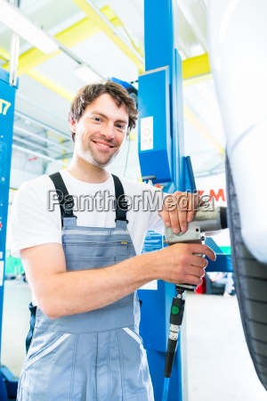 mechanic tire change in car workshop