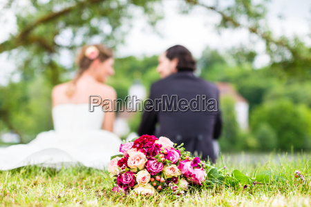 bridal pair with bouquet sitting on
