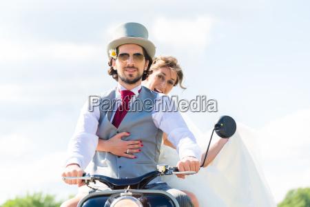 bridal pair driving motor scooter wearing