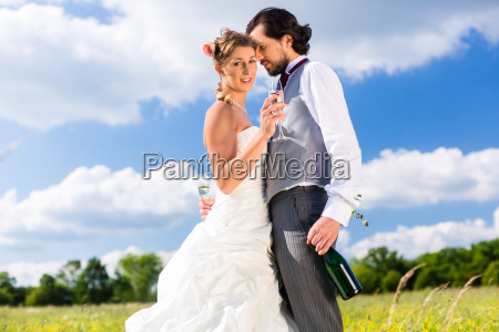 wedding couple on meadow kissing