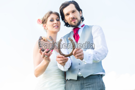 wedding couple showing horse shoe for