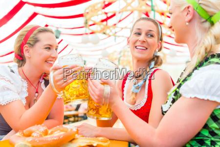 friends drinking bavarian beer at oktoberfest