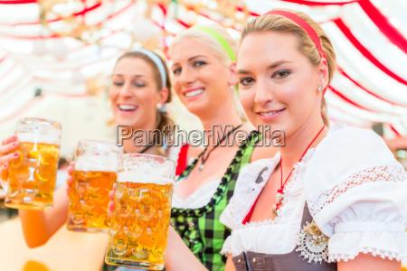 freunde trinken bayerisches bier auf oktoberfest