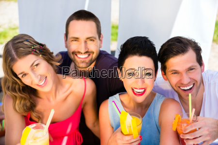 group of friends drinking cocktails in