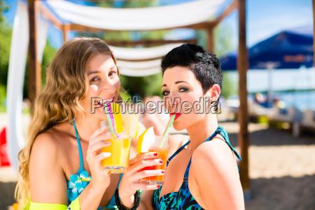two women in beach bar drinking