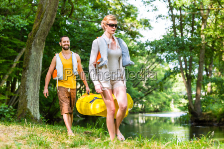 woman and man carrying together kayak