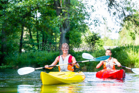 friends paddling with canoe on forest