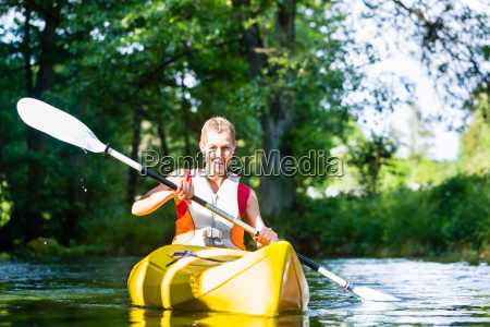 woman paddling with canoe on forest