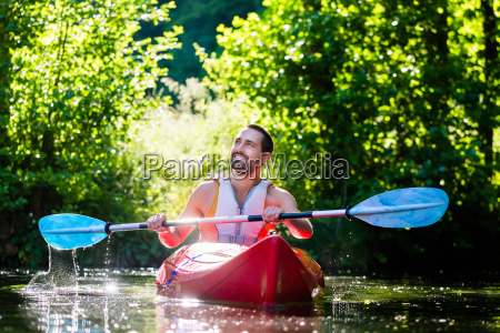 man paddling with kayak on river