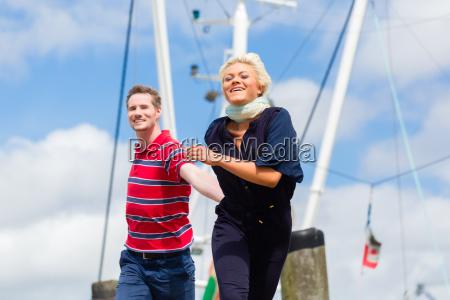 couple running at marina pier