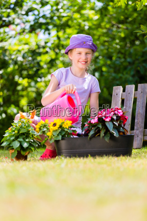 child watering flowers in garden