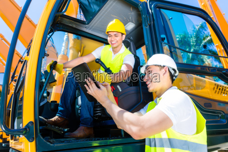 asian construction driver discussing with engineer
