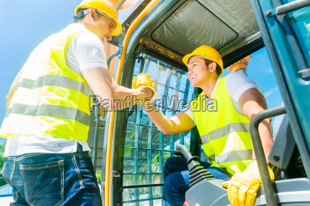 two asian workers with excavator on