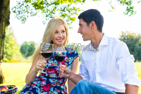 couple having picnic wit red wine
