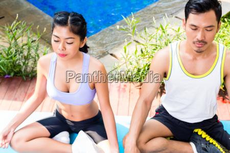 asiatische paar in lotus sitz yoga