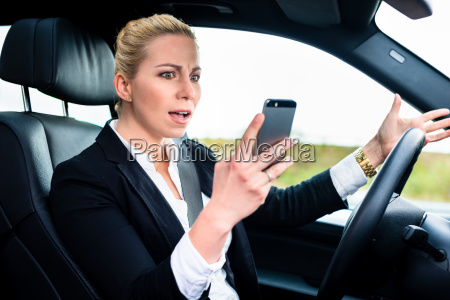 woman texting while driving by car
