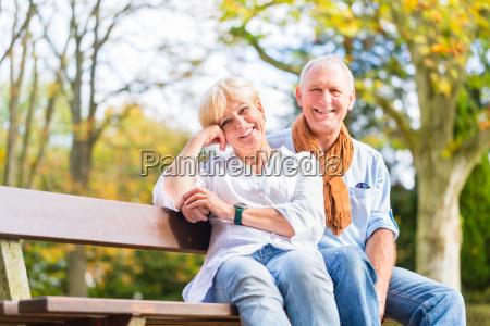 seniorenpaar sitzt im herbst auf teilbank