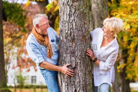 aelteres paar flirten spielen um baum