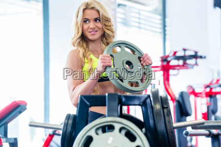 woman taking weights from stand in