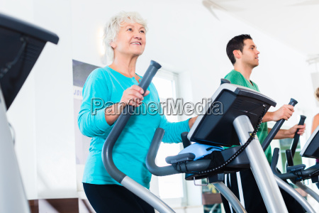 senior woman on elliptical trainer exercising