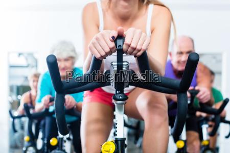 senior people in gym spinning on