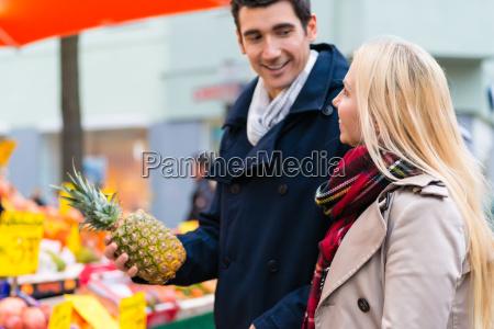 ehepaar kauft lebensmittel auf bauernmarkt