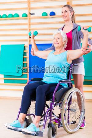 aeltere frau im rollstuhl der physiotherapie