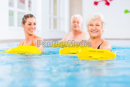 aeltere und junge menschen in wassergymnastik