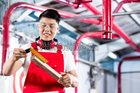 asian carpenter measuring piece of wood