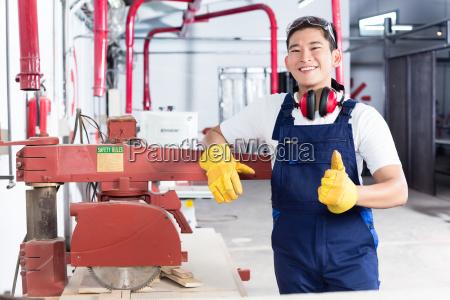 proud asian carpenter showing thumbs up
