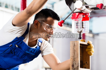 asian worker on drill in production