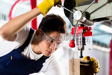arbeiter auf bohrmaschine in der werkstatt
