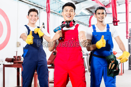 three asian industrial workers proud in