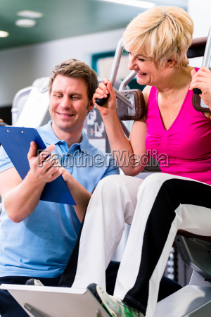 trainer in gym assisting senior woman