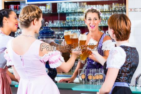 gastwirt und gaeste trinken bier in