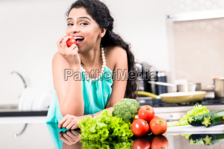 indian woman eating healthy apple in