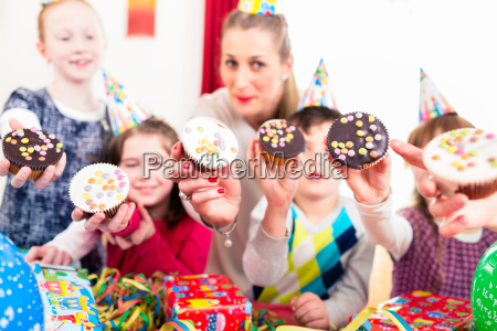 kids showing muffin cakes at birthday