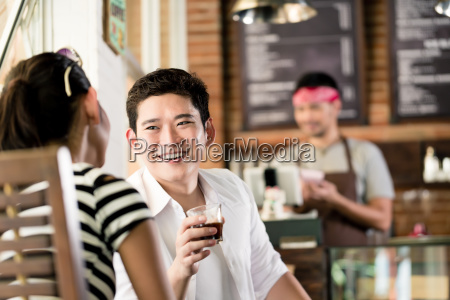 asian couple in cafe flirting while