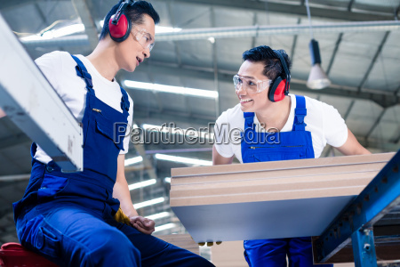 asian carpenters in wood workshop at