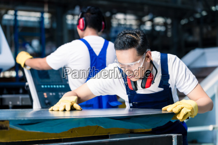 team of workers with metal sheets