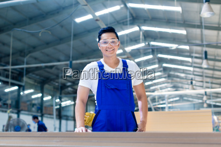 asian carpenter standing in workshop with