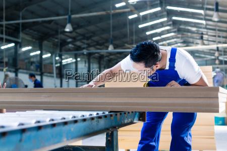 carpenter in asian wood workshop working
