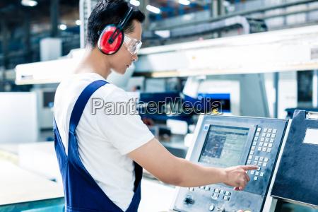 worker entering data in cnc machine
