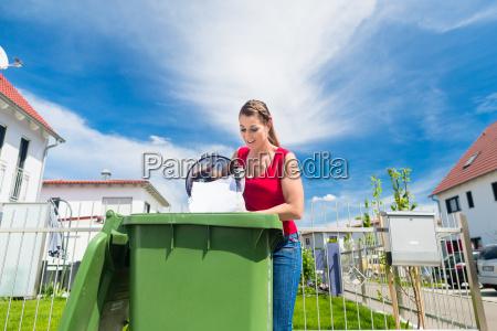 frau entleert papiermuell und altpapier in