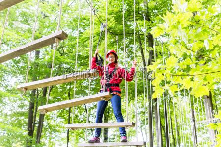 kid walking auf seilbruecke im kletterkurs