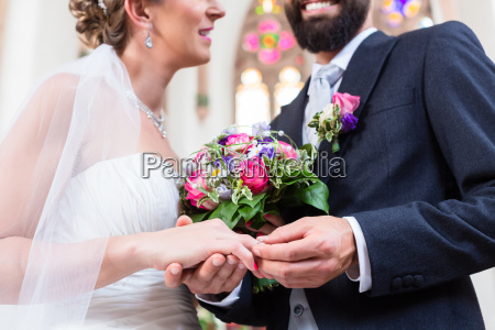 groom slipping ring on finger of