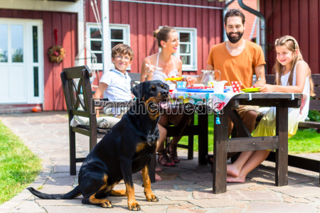 family with dog eating in garden