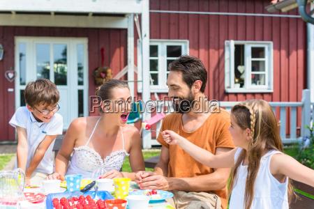 family having coffee in garden eating