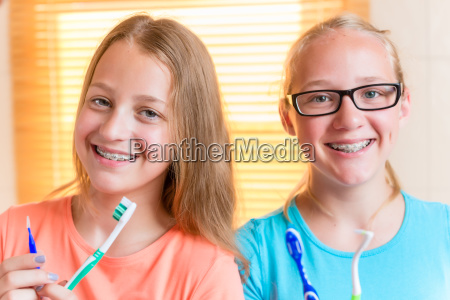 zwei maedchen mit zahnaerztlichen halterungen zaehneputzen